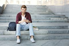 Student sitting on stairs and using his smartphone outdoors. Student sitting on grey stairs and listening to music on his smartphone outdoors, having a rest in Royalty Free Stock Photography