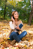 Student sitting with headphones among maple leaves. And smiling Royalty Free Stock Photos