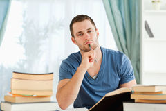Student sitting at his desk doing his homework Stock Images