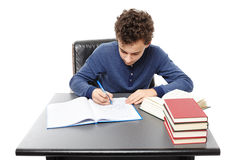 Student sitting at his desk focused and doing his homework Royalty Free Stock Photography