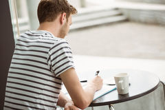 Student sitting with a hot drink and writing on notepad Stock Photography