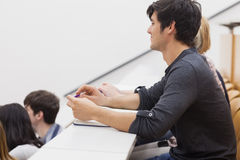 Student sitting in a lecture hall and listening the teacher Stock Image