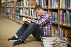 Student sitting on library floor reading Stock Photography