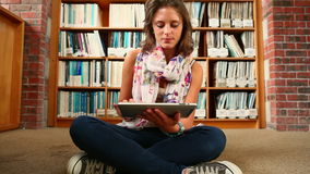 Student sitting on library floor using tablet stock footage