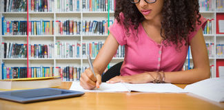 Composite image of student sitting in library writing. Student sitting in library writing against multi colored bookshelf in library Royalty Free Stock Photo