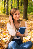 Student sitting and looking at camera. Student sitting with headphones among maple leaves and looking at camera royalty free stock image