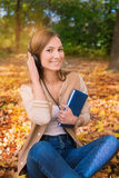Student sitting among maple leaves, listening to headphones and. Holding one book royalty free stock photo