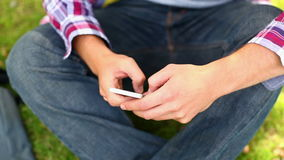 Student sitting outside texting on the phone Royalty Free Stock Photography