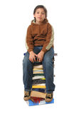 Student sitting on a pile of books. Boy sitting on a big pile of books. Different expressions (series stock image