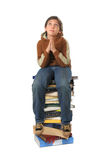 Student sitting on a pile of books. Boy sitting on a big pile of books. Different expressions (series stock photography