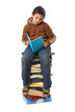 Student sitting on a pile of books. Boy sitting on a big pile of books. Different expressions (series royalty free stock photo
