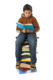 Student sitting on a pile of books. Boy sitting on a big pile of books. Different expressions (series royalty free stock photography