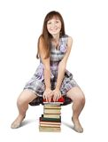 Student sitting on pile of books Stock Photo