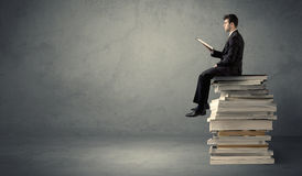 Student sitting on pile of books Stock Photography