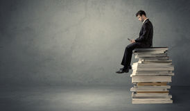 Student sitting on pile of books Stock Image