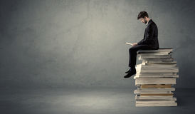 Student sitting on pile of books Royalty Free Stock Photography
