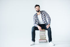Student sitting on pile of books on white with copy space Royalty Free Stock Photo