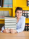 Student Sitting With Piled Books In University. Portrait of handsome male student sitting with piled books in university library Stock Photo