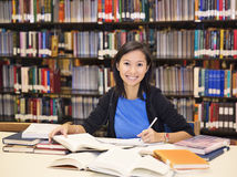 Student sitting and reading book in library Royalty Free Stock Image