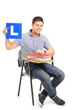A student sitting on a school chair and holding a L plate Royalty Free Stock Photo