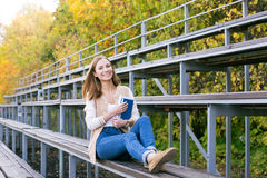 Student sitting on sport tribune with book. S stock photo