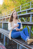 Student sitting on sport tribune and smiling at camera. On the sunset stock photo