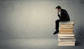 Student sitting on stack of books Royalty Free Stock Images