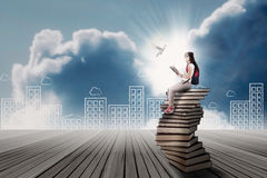 Student sitting on a stack of books Stock Image