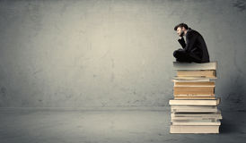 Student sitting on stack of books Royalty Free Stock Photography