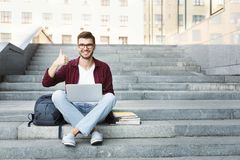Student sitting on the stairs showing thumb up outdoors. Happy student sitting on the stairs showing thumb up working on laptop, in the university campus Stock Image