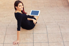 Student sitting on stairs with a tablet computer Royalty Free Stock Image