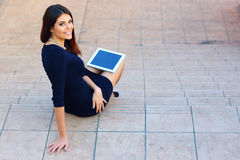 Student sitting on stairs with a tablet computer Stock Images