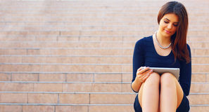Student sitting on stairs with a tablet computer Stock Photo