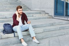 Student sitting on stairs and using smartphone. Student sitting on grey stairs and listening to music on his smartphone outdoors, having rest in university Stock Photo