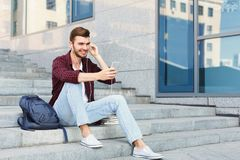 Student sitting on stairs and using smartphone. Student sitting on grey stairs and listening to music on his smartphone outdoors, having rest in university Royalty Free Stock Images