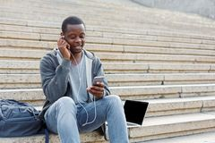 Student sitting on stairs and using smartphone. Student sitting on grey stairs and listening to music on his smartphone outdoors, having rest in university Royalty Free Stock Image