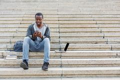 Student sitting on stairs and using smartphone. Student sitting on grey stairs and listening to music on his smartphone outdoors, having rest in university Royalty Free Stock Photo