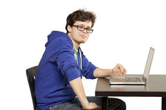 Student sitting at table using computer. Relaxed Royalty Free Stock Images