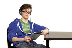 Student sitting at table using computer. Relaxed Stock Images