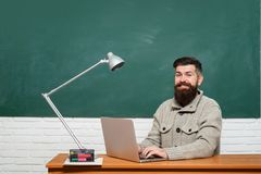 Student sitting at table and writing on notebook. Teacher teaches a student. School day. Science and education concept. Bearded teacher royalty free stock photography