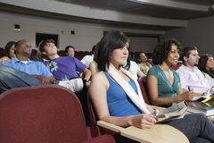 Student Sitting Together In Classroom. Group of multiethnic students sitting together in classroom Stock Photo
