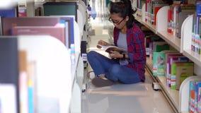 Student sitzt in der Bibliothek während Lesebuch stock footage