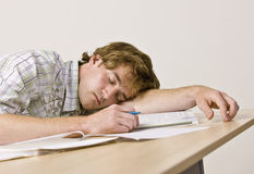 Student sleeping at desk in classroom. Student naps while sleeping at a desk with schoolwork Royalty Free Stock Photos