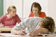 Student sleeping at desk in classroom. Male student takes a nap while in class Royalty Free Stock Photos
