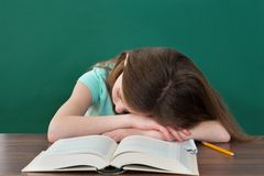 Student Sleeping At Desk. Tired Student With Books And Pencil Sleeping At Desk In Classroom Royalty Free Stock Photography