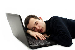 Student sleeping on floor with laptop in his hand Royalty Free Stock Image