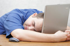 Student sleeping on his laptop. The student works on a portable computer Royalty Free Stock Images