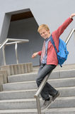 Student sliding down railing on stairway Stock Images