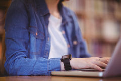 Student with smartwatch using laptop in library Stock Photos