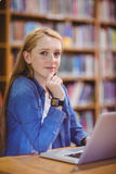 Student with smartwatch using laptop in library Stock Images